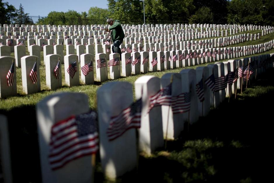 worker-places-u-s-flags-at-graves-at-cypress-hills-national-cemetery-in-brooklyn-new-york